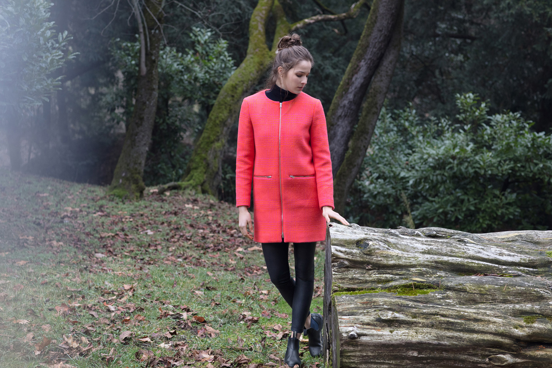 Frau in aprikosefarbenen Mantel steht im Wald neben einem Baumstamm
