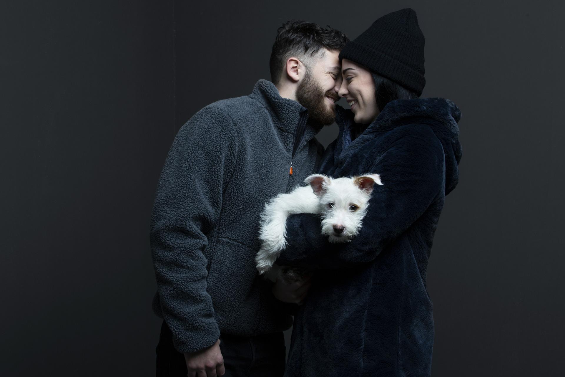 Mann und Frau mit Hund in kuscheligen Winterjacken